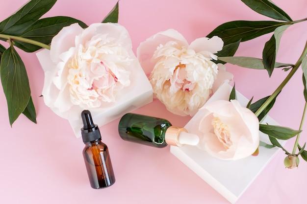 Dwie szklane butelki z zakraplaczem do użytku medycznego i kosmetycznego oraz białe kwiaty piwonii delikatny kwiat na różowym tle. pielęgnacja skóry i koncepcja spa.