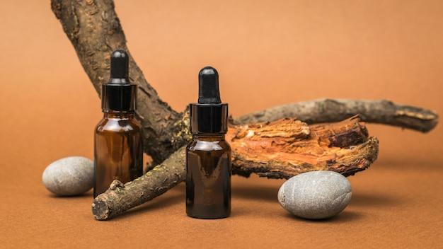 Dwie szklane butelki z zakraplaczem, kamienie i stare drzewo na brązowym tle. kosmetyki i produkty lecznicze na bazie naturalnych minerałów.