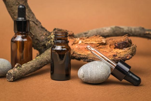 Dwie szklane butelki z zakraplaczem, stare drzewo i kamień na brązowym tle. kosmetyki i produkty lecznicze na bazie naturalnych minerałów.