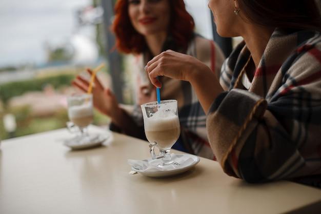 Dwie szklane filiżanki cappuccino na stole. portret dwóch dziewczyn pije kawę w kawiarni z bliska. szklanka cappuccino ze słomką w rękach kobiety. dziewczyny mówią za filiżanką aromatycznej kawy.