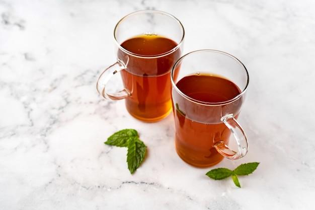 Dwie szklane filiżanki czarnej herbaty na tle białego marmuru. widok z góry