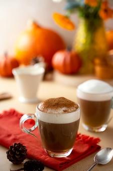 Dwie szklane filiżanki dyniowego jesiennego ciepłego napoju latte z bitą śmietaną. jesienny przytulny napój.