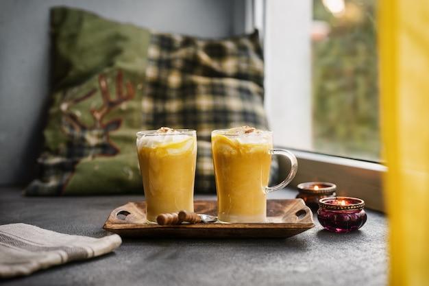 Dwie szklane filiżanki dyniowej przyprawy latte obok okna