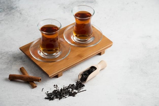 Dwie szklane filiżanki herbaty z laseczkami cynamonu i herbatkami sypkimi.zdjęcie wysokiej jakości