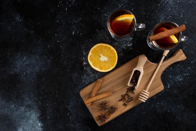 Dwie szklane filiżanki herbaty z laskami cynamonu i drewnianą łyżką.