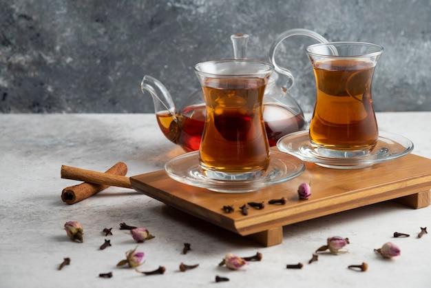Dwie szklane filiżanki herbaty z laskami cynamonu i suszonymi różami.