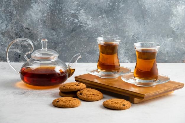 Dwie szklane filiżanki herbaty z pysznymi ciasteczkami.