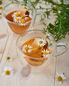 Dwie szklane filiżanki herbaty z rumiankiem na drewnie