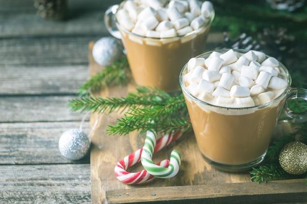 Dwie szklane filiżanki kakao z pianką marshmallow na drewnianym z dekoracjami świątecznymi