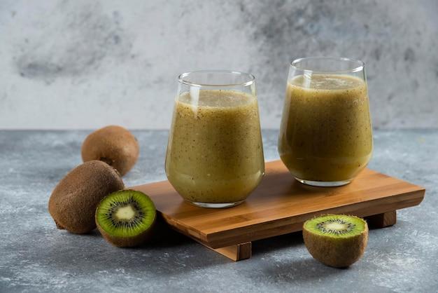 Dwie szklane filiżanki smacznego soku z kiwi na desce.