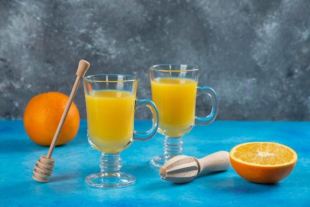 Dwie szklane filiżanki soku pomarańczowego z drewnianym rozwiertakiem.