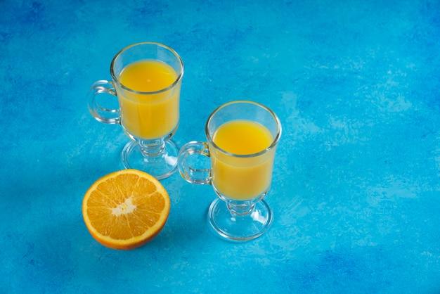 Dwie szklane filiżanki soku z plasterkiem pomarańczy.