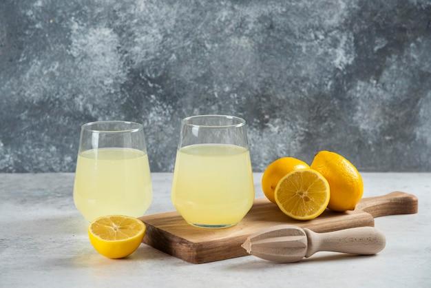 Dwie szklane filiżanki świeżej lemoniady na drewnianej desce.