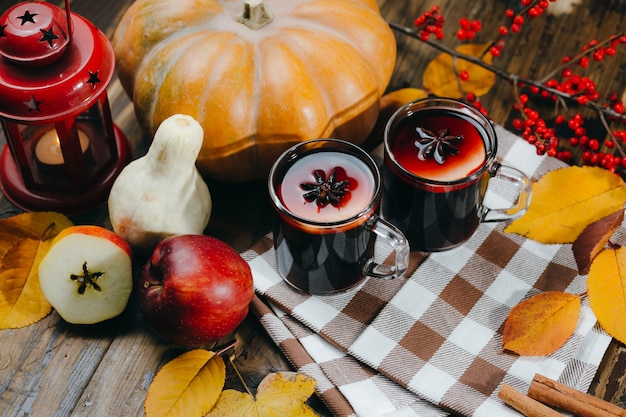 Dwie szklane filiżanki z grzanym winem z cytrusami, jabłkiem i przyprawami na srebrnej tacy z cynamonem i kwiatkiem bawełny.