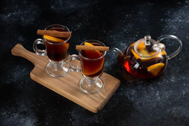 Dwie szklane filiżanki z pyszną herbatą i laskami cynamonu.