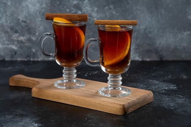 Dwie szklane filiżanki ze świeżą herbatą i laskami cynamonu.