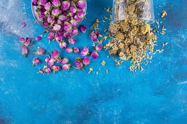 Dwie szklane miski suszonych kwiatów na niebieskim stole.