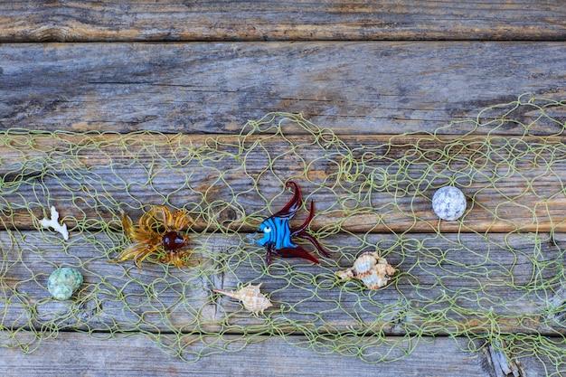 Dwie szklane ryby dekoracyjne, muszle, rozgwiazdy w sieci na drewnianym tle.