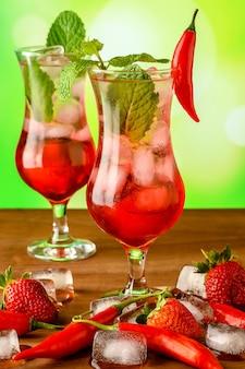 Dwie szklane szklanki z koktajlem z grenadyny ozdobione pieprzem i miętą na drewnianym stole