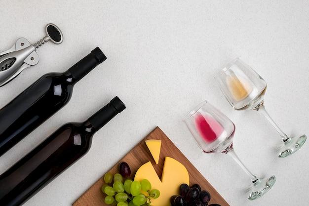 Dwie szklanki białego i czerwonego wina sera i winogron widok z góry