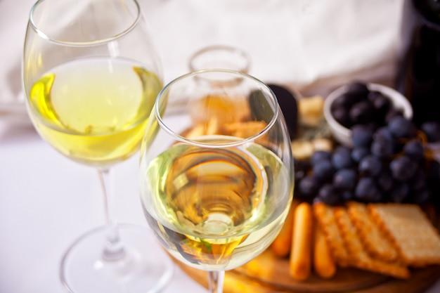Dwie szklanki białego wina i talerz z różnymi serem i owocami