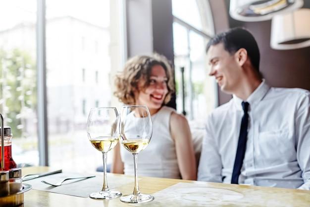 Dwie szklanki białego wina na stole w restauracji. w tle roześmiana para zakochanych