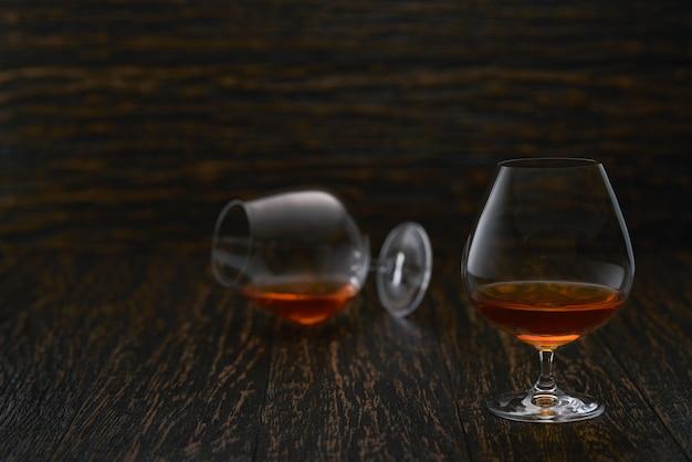 Dwie szklanki bourbonu lub szkockiej lub brandy na drewnianym stole.
