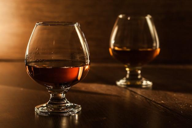 Dwie szklanki brandy na drewnianym stole.