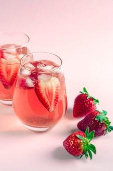 Dwie szklanki chłodzącej sangrii truskawkowej z winem musującym, truskawką, kostkami lodu w kieliszku do szampana