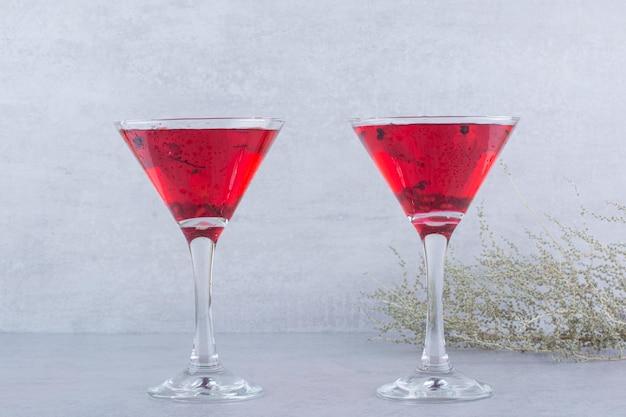 Dwie szklanki czerwonego soku na tle kamienia. zdjęcie wysokiej jakości