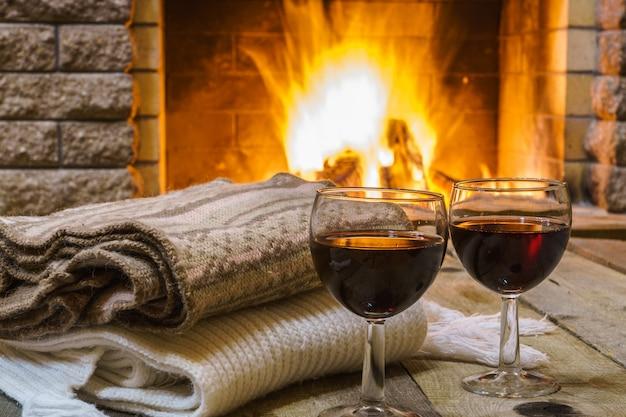 Dwie szklanki czerwonego wina i rzeczy wełnianych w pobliżu przytulnego kominka, w wiejskim domu, w zimie
