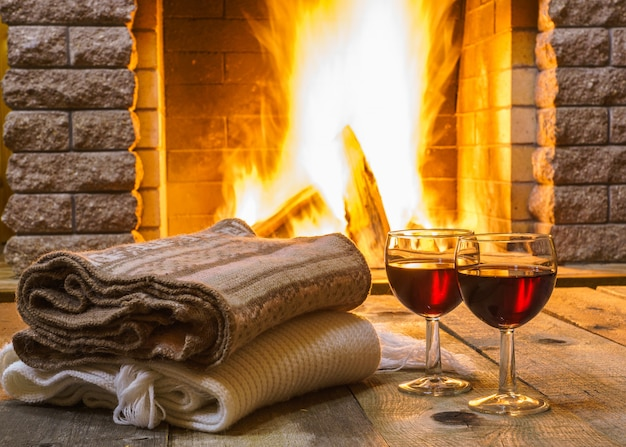 Dwie szklanki czerwonego wina i rzeczy wełnianych w pobliżu przytulnego kominka