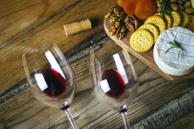 Dwie szklanki czerwonego wina i talerz serów widok z góry