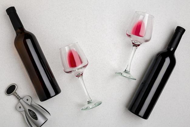 Dwie szklanki czerwonego wina i winogron. dwie butelki wina i korkociąg. widok z góry z miejscem na kopię