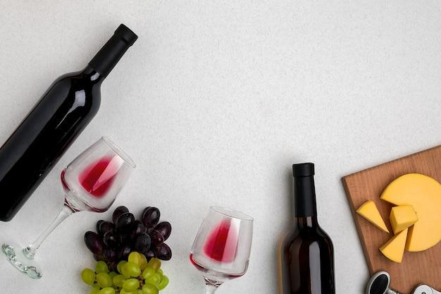 Dwie szklanki czerwonego wina sera i winogron widok z góry