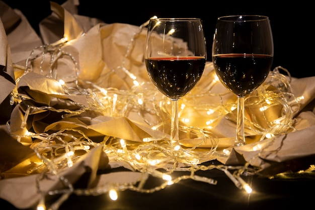 Dwie szklanki czerwonego wina stoją w lśniącej girlandzie. koncepcja romantycznej daty. koncepcja uroczystości