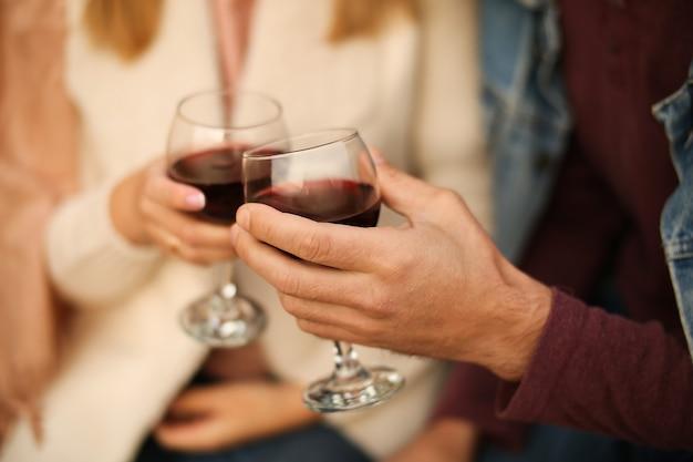 Dwie szklanki czerwonego wina z bliska w ręce poza domem. mężczyzna i kobieta brzęczą okularami.