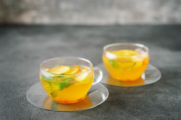 Dwie szklanki filiżanek herbaty owocowej na ciemnej powierzchni