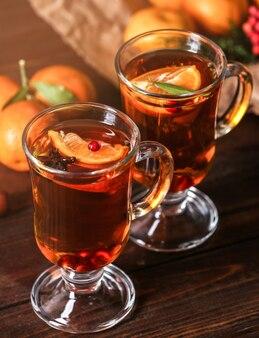 Dwie szklanki gorącej herbaty mandarynki na drewnianym stole