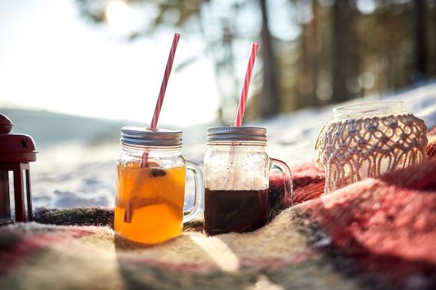Dwie szklanki grzanego wina stoją na kocu w zimowym lesie sosnowym