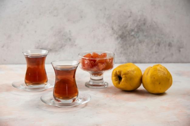Dwie szklanki herbaty, dżem i owoce pigwy na marmurowym stole.