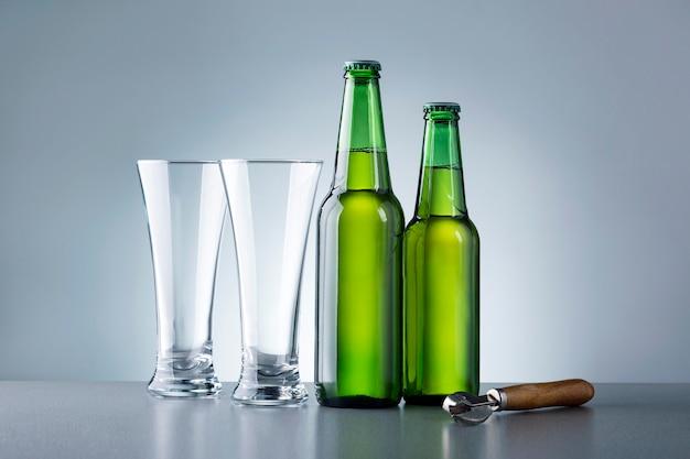 Dwie szklanki i butelki piwa na szarym tle. napoje bezalkoholowe.