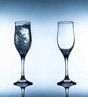 Dwie szklanki, jedna z nich z wodą
