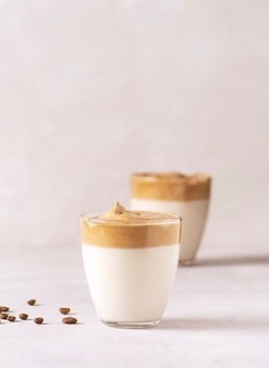 Dwie szklanki kawy dalgona stoją na szarym betonowym stole, obok ziaren kawy.