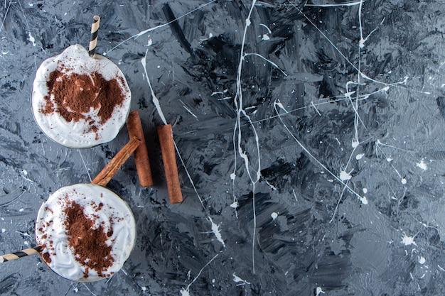 Dwie szklanki kawy z bitą śmietaną na marmurowej powierzchni.