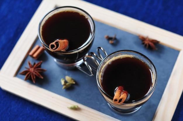 Dwie szklanki kawy z przyprawami i canellą