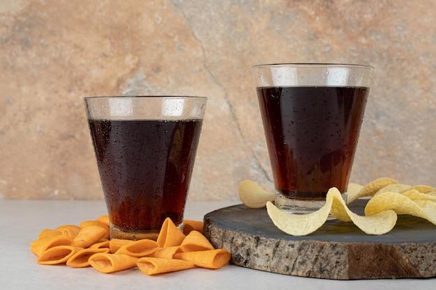 Dwie szklanki koktajli z różnymi chrupiącymi frytkami
