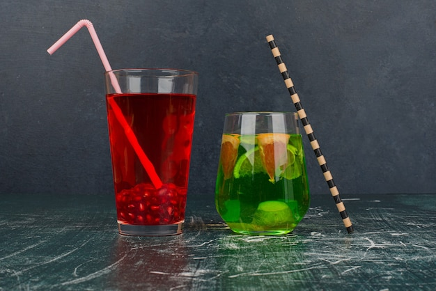 Dwie szklanki koktajli ze słomkami na marmurowym stole.