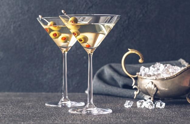 Dwie szklanki koktajlu martini przyozdobionym zielonymi oliwkami