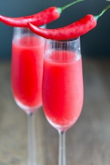 Dwie szklanki koktajlu mimosa ozdobione papryczkami chili